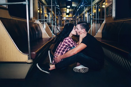 Young man and woman use underground. Couple in subway. Lovely cheerful couple sit together on floor and kissing. Alone in empty underground carriage. Love story. Urban modern view. 版權商用圖片 - 121641538