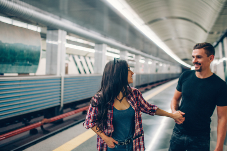 Young man and woman use underground. Couple in subway. Young man follow woman and hold her hand. They look at each other and smile. Love story. 版權商用圖片 - 121641730