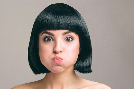 Young woman with black hair posing on camera. Expressive emotional model with bob haircut. Isolated on light background. Studio shot. Mouth full of air.