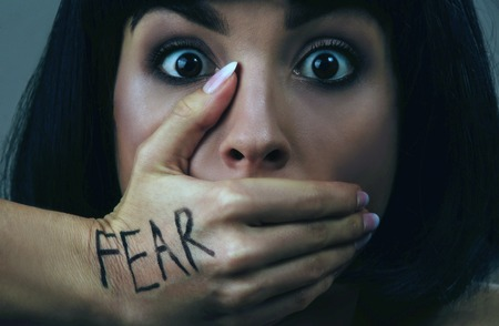 Young scared woman with black hair posing on camera. Scared brunette afraid. She look straight. Mouth closed with hand. Fear and despair. Isolated on blue background. 版權商用圖片