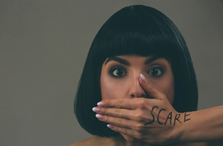 Young scared woman with black hair posing on camera. Scared afraid model look straight. Mouth closed with hand. Fear in eyes. Bob haircut. Isolated on dark background. 版權商用圖片