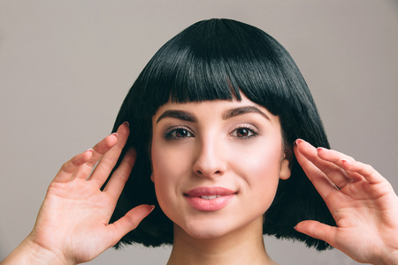 Young woman with black hair posing on camera. Attractive brunette with bob haircut. Model touching it with both hands. Isolated on light background in studio. 版權商用圖片 - 122203216