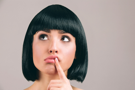 Young woman with black hair posing on camera. Amazed thoughtful model look up to left and hold finger on lips. Brunette bob haircut. Isolated on light background. 版權商用圖片 - 122203221