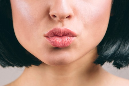 Cut view of beautiful lips with lipstick on. Young brunette with bob haircut. Kiss. Naked neck. Isolated on light studio background.