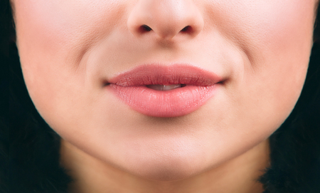 Close up of nice young womans lips smiling a bit. Short black hair. Healthy skin. Cut view.