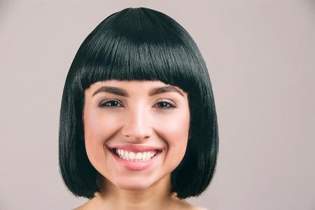 Jonge vrouw met zwart haar die zich voordeed op camera. Vrolijke mooie modelglimlach. Zwart bob kapsel. Geïsoleerd op lichte achtergrond. Stockfoto