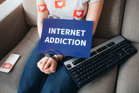 Young woman have social media addiction. Sitting on sofa. Hands are wrapped. Keyboard besides. Internet addiction. Cut view. 版權商用圖片