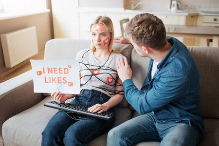 Young woman have social media addiction. Sitting on sofa emotionless. Body wrapped with cord. Hands on keyboard. Young man touch her. Woman hold paper I need likes.