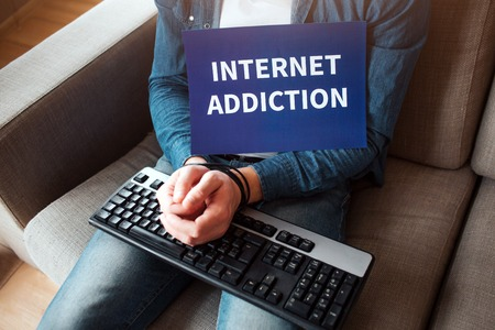Young man and woman have social media addiction. Hostage of social media. Chains around wrist. Internet addiction.