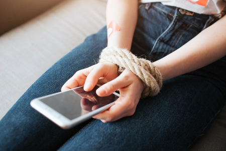 Young woman have social media addiction. Sitting on sofa. Phone in hands. Rope around wrist. Hostage of social media. Cut view. 版權商用圖片 - 122818044