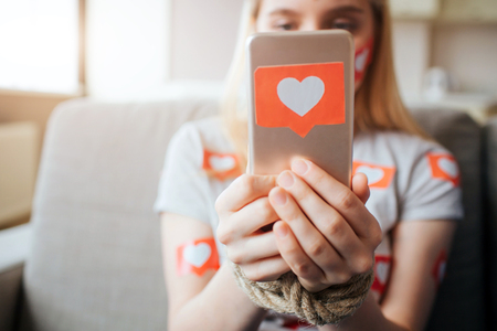 Young woman have social media addiction. Sitting on sofa and holding phone in hands. Like symbol. Heart shape. Daylight.