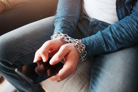 Young man have social media addiction. Phone in hands. Chains around wrist. Hostage of social media. Sitting on sofa. Cut view. 版權商用圖片