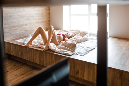 Seductive young naked dark-haired woman in bed on morning. Slim hot model lying alone. Well-built beautiful legs. Woman wear red lingerie. Masturbation. Sensual picture. Stockfoto