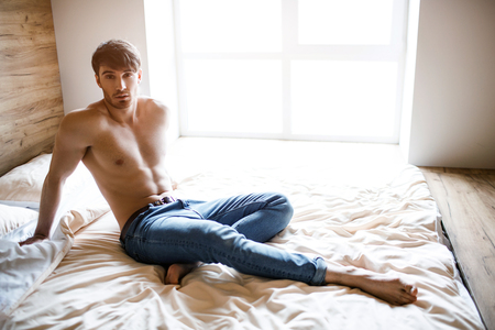 Relaxed calm and peaceful young man sitting on bed and posing on camera. Attractive handsome well-built slim guy look straight. Alone in room. Daylight. Banco de Imagens
