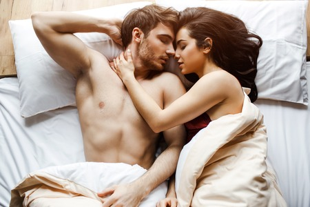Los pares jovenes tienen en la cama. Acostados juntos muy cerca. Modelo femenino abrazo chico. Acostado con los ojos cerrados. Sexo en la cama. Almohadas blancas. Dormido. Foto de archivo