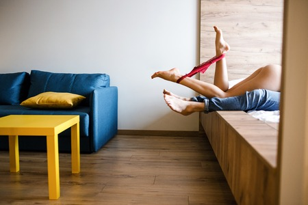 La giovane coppia ha sul letto. Vista di taglio della biancheria intima della donna tra le gambe in posa sulla macchina fotografica. Modello sdraiato sull'uomo. Archivio Fotografico
