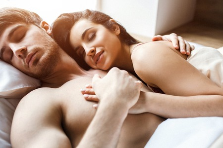 Young couple after on bed. Sleeping and dreaming together. Satisfied young people happy and delightful. Woman embrace man. He hold her hand in his. Attractive models.