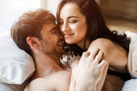 Young sexy couple have intimacy on bed. Beautiful picture of woman lying on man and smile. Spend time together in bed. Nice tender people.