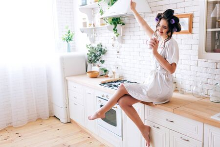 Young careless housewife stretching hand up and enjoying life. Hold cup in hand. Curlers in hair. Alone in kitchen. Sugar daddy pays for everything. Wearing white dressing gown.