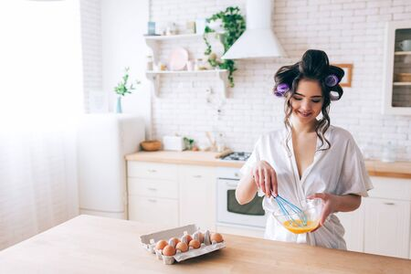 Young beautiful female housekeeper cooking in kitchen. Blending eggs in glass bowl. Look down and smile. Curlers in hair. Alone in kitchen. Daylight. Wear white dressing gown.