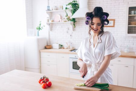 Young female housekeeper stand at desk in kitchen and cut green onion. Work careful. Cut red pepper on left side. Alone in kitchen. Working at home. Sugar daddy pays for everything.