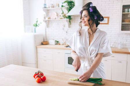 Cheerful positive young woman stand in kitchen and look at window. Cut green onion on desk. Female housekeeper wear white dressing gown. Alone in kitchen. Red pepper on left side.