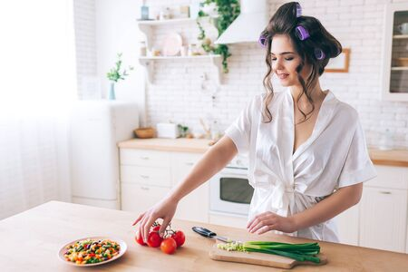 Attractive nice young woman cooking in kitchen. Stand at desk and take cut red pepper. Green onion is cut on desk. Vegetables mix on plate. Working at home. Careless life.