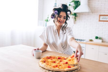 Cheerful nice happy woman with curlers in hair taking pice of pizza inkitchen. Morning daylight. Carefree person without work. Life is good. Sugar daddy pays for everything. 版權商用圖片