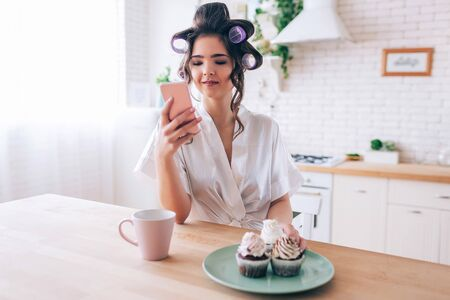 Calm peaceful young woman look at phone in hand. Cup of drink with pancakes on plate on table. Alone in kitchen. Housekeeper with curlers in hair live careless life.