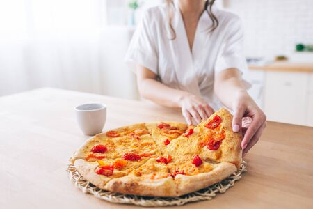Cut view of woman in white dressing gown in kitchen. Taking piece of pizza. Small slice. Young housekeeper live carefree life. 版權商用圖片