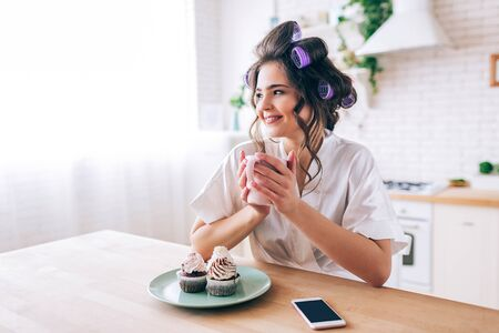 Beautiful young female housewife in kitchen. Holding cup and look to side. Smiling alone. Pancakes and phone on table. Carefree young woman living beatufiul rich life. No work.