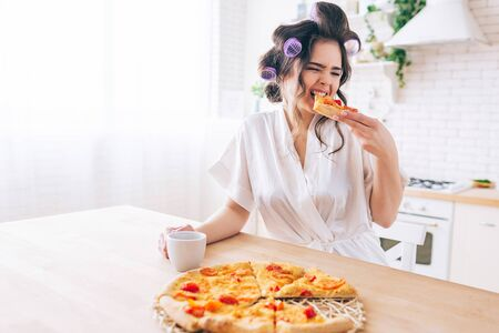 Hungry young housewife sit in kitchen and eat pizza. Bite slice of food. Alone in room. Housekeeper enjoy life without work. Hold cup in hands.