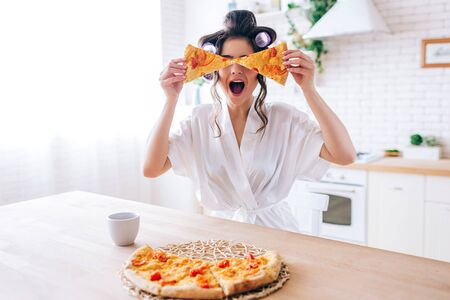 Excited happy young woman in kitchen plaing with pizza slices. Cover eyes with food. Carefree housekeeper very playful. Wear white dressing gown. Careless houseswife. 版權商用圖片