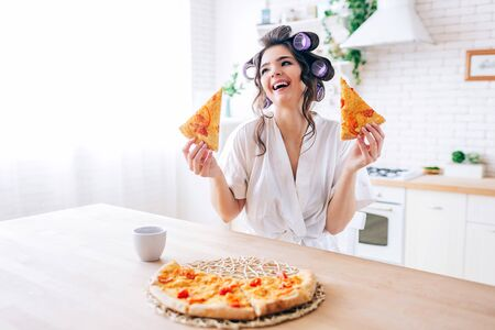 Positive emotional young carefree housekeeper in kitchen. Holding two slices of pizza and smile. Cup on table. Alone in kitchen. Life without work. 版權商用圖片