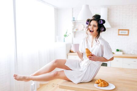 Happy attractive nice young housekeeper sit on table in kitchen. Laughing out loud. Holding white cup in hands. Posing on camera. Carefree woman on picture. 版權商用圖片