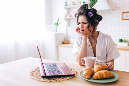 Amazed wondered young woman look on laptop. Watching movie in kitchen. Croissant and cup of drink on table. Careless housekeeper in room. Life withour work. Daylight in morning. 版權商用圖片