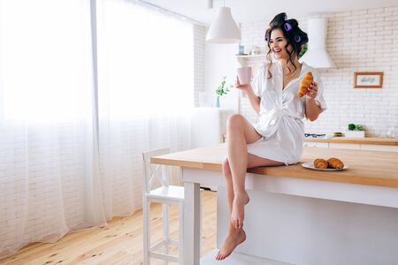 Positive cheerful young woman on table in kitchen. Carefree housekeeper holding cup and croissant in hands. Smile. Alone in kitchen. Sugar daddy pays for everything. 版權商用圖片