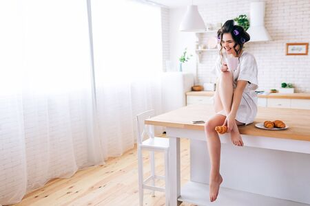 Cheerful careless young woman with curlers in haor. Sitting on table in kitchen and laughing. Hold cup in hand. Phone and plate with croissants on table. Life without work. Careless. 版權商用圖片