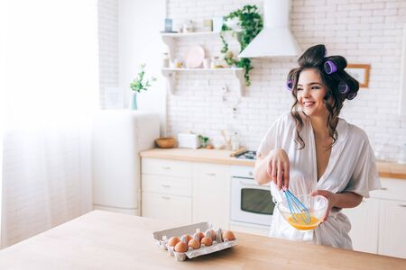 Beautiful cheerful nice young housewife blending eggs in kitchen. Looking to side and smile. Eggs in container on table. Careless wife without work. Daylight. 版權商用圖片