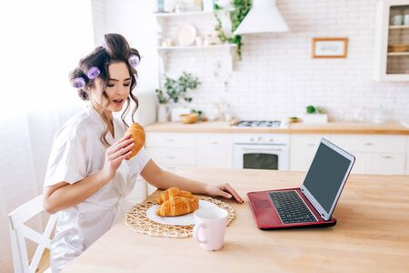 Young carefree housekeeper sit at table and eat croissant. Working from home. Laptop and cup of drink on table. Alone in kitchen. Sugar daddy pays for everything.