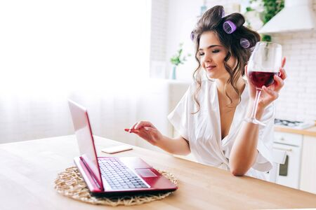Picture of beautiful housekeeper watching movie on laptop and drink wine in kitchen. Work at home. Careless housewife. Home alone. Curlers in hair. 版權商用圖片