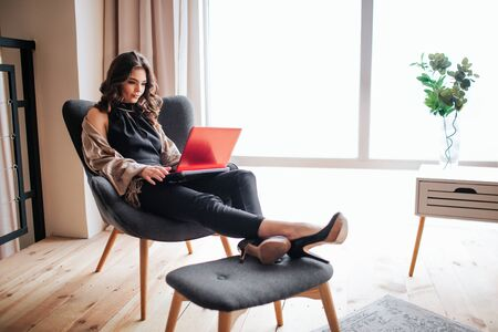 Young businesswoman work at home. Remote work. Sitting on chair and typing on laptops keyboard. Alone in living room. Busy stylish fashionable brunette. 版權商用圖片
