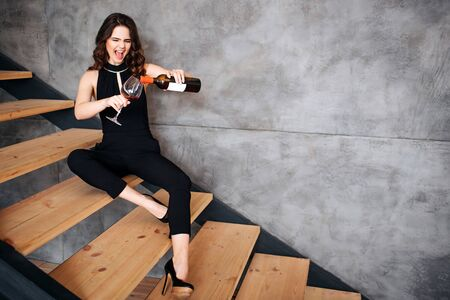 Young woman has problems with alcohol. Stylish model sitting on steps and pouring wine into glass. Emotional brunette having fun. 版權商用圖片