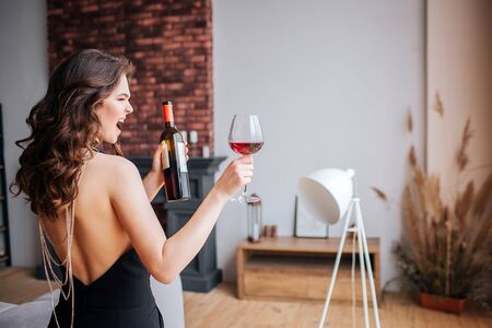 Young woman has problems with alcohol. Beautiful well-built and slim model in black suit hold bottle and glass with wine. Standing back and screaming. Alone in living room. 版權商用圖片