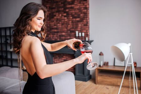 Young woman has problems with alcohol. Model in black beautiful suit pouring red wine from bottle into glass. Female sommelier.