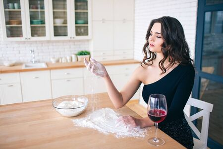 Young beautiful woman cooking food. Sitting at table and holding flour in hand. Look at it. Calm and peaceful model in kitchen. Wine glass beside.