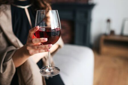 Cut view of womans hand holding glass of red wine. Model wear black dress and brown shawl. Woman in living room alone. 版權商用圖片