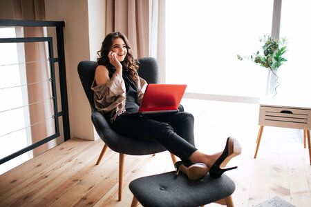 Young businesswoman work at home. Busy model sitting in chair and holding legs on small stool. Talking on phone. Busy lady hold laptop on knees. Remote work. Alone in living room.