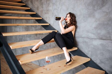 Young woman has problems with alcohol. Sitting on steps and drink wine fron bottle. Alone. Hangout and depression. Problems with behaviour.