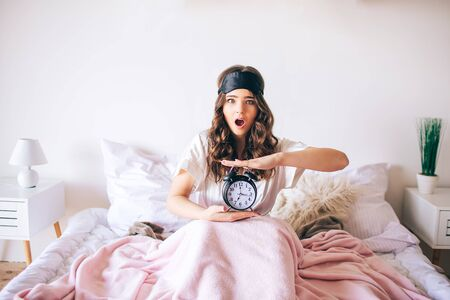 Dark haired beautiful young brunette wake up in her bed. Confused woman hold clock in hands. Woke up later. Amazed model look on camera with wonder. Bedroom.